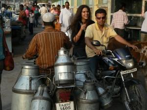 Un porteur de lait a moto croise un scooter dans la ville sainte